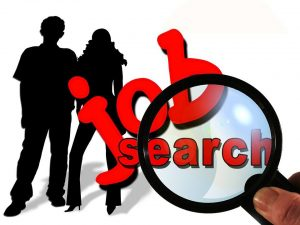 """Illustration: Magnifying glass highlighting the words """"job search"""" with silhouettes of two people in the background."""