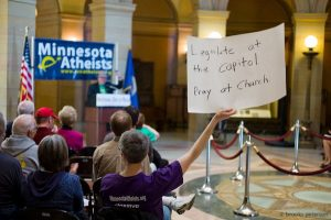 """Photo of audience in the capitol rotunda facing a podium in front of a Minnesota Atheists banner. An audience member holds up a sign reading, """"Legislate at the capitol. Pray at church."""""""