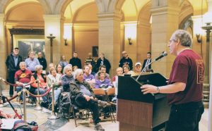 Photo of August Berkshire at a podium in the state capitol rotunda addressing a seated and standing audience.