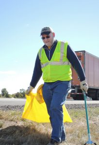 Photo of man in reflective vest by the side of the highway, with garbage bag and grabber tool.