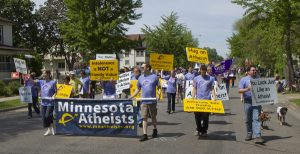 Photo of Minnesota Atheists marching in a parade with a banner and several handheld signs.