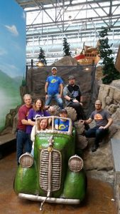 Photo of small group of people at Mall of America amusement park in and around an antique car photo area.