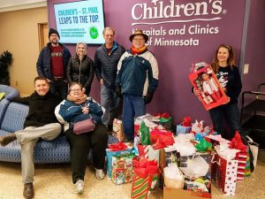 Photo of a group of people in winter outerwear, with wrapped and unwrapped presents, in front of Children's Hospital sign.