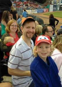 Photo of two adults with small children in bleachers.
