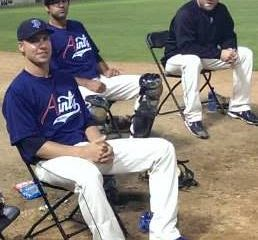Three baseball players in Aints attire sit in chairs at the edge of the field.