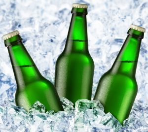 Photo of three green, capped glass bottles in ice.