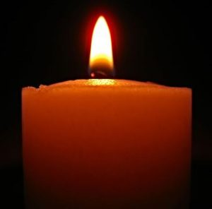 Photo of a burning votive candle against a dark background.