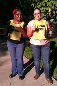 Photo of two women wearing yellow clinic escort vests and givings thumbs up.