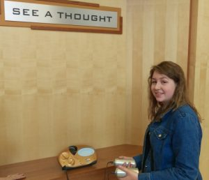 """Photo of a young woman, smiling dubiously, hold two metal handles attached to something that looks like a modern art game console. Sign on the wall says, """"See a thought."""""""