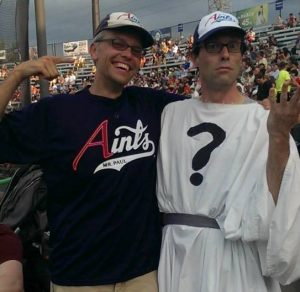 Man in Aints t-shirt poses with actor in white robe with a question mark on the front (Doubting Thomas). Both wear Aints caps.