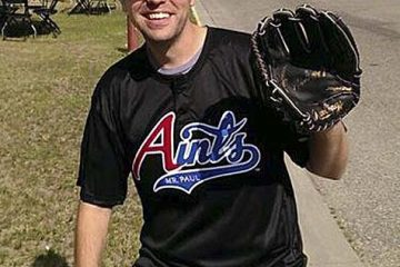 Photo of Eric in Aints t-shirt and cap, wearing a baseball glove.