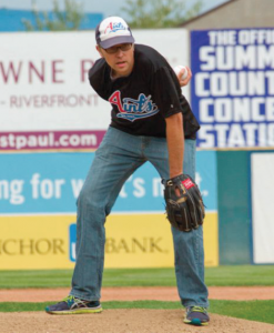 Photo of man with Aints t-shirt and cap on a pitching mound, holding a baseball behind his back.
