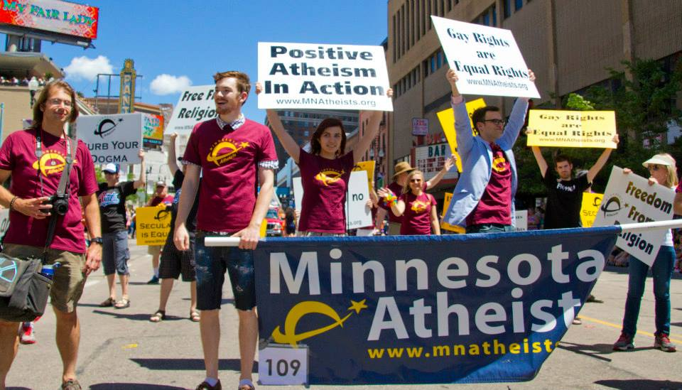 "Group of people marching behind Minnesota Atheists banner with handheld signs reading, ""Positive atheism in action"" and ""Gay rights are human rights."""