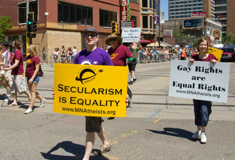 "Group of people marching in parade with handheld signs reading, ""Secularism is equality"" and ""Gay rights are human rights."""