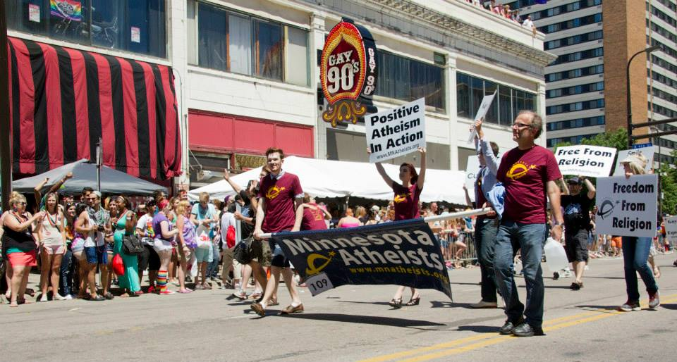 People marching behind Minnesota Atheist banner with handheld signs outside the Gay 90's.