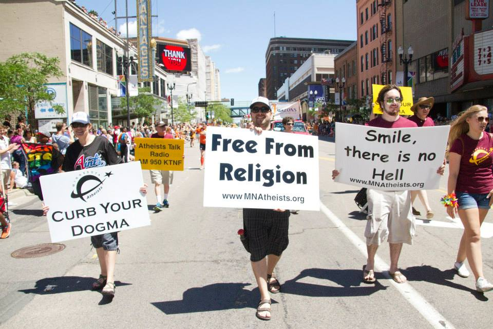 "Group of people marching in parade with handheld signs reading, ""Curb your dogma"", ""Free from religion"", and ""Smile, there is no Hell."""
