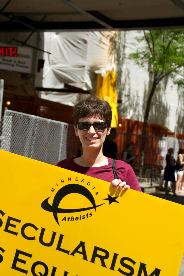 Smiling woman carrying obscured sign in parade.