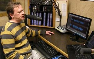 Photo of man in striped sweater speaking into a microphone in front of a computer monitor.