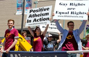 """Photo of marchers in parade with MNA signs reading """"Positive Atheism in Action"""" and """"Gay Rights Are Equal Rights."""""""