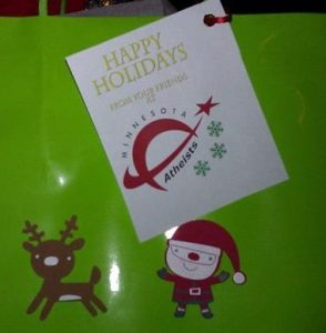 Photo of wrapped present with cartoon Santa and reindeer and gift tag from Minnesota Atheists.