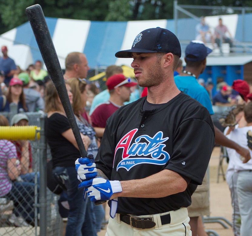 Photo of baseball player in Mr. Paul Aints jersey looking at his back. Crowd in the background.