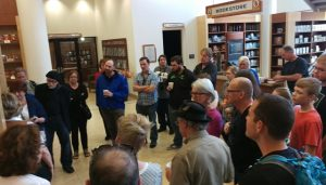 Photo of group of about 25 people listening to a speaker in a space that looks like a library of museum.