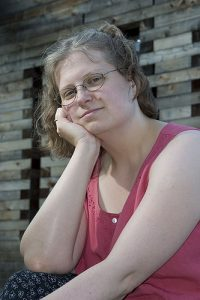 Photo of woman in glasses resting her chin on her hand.