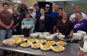 Photo of a group standing behind a table full of prepared food in a commercial kitchen.