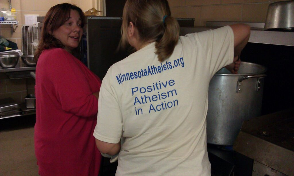Two volunteers working in a commercial kitchen