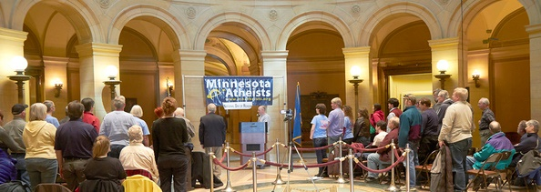 Photo of gathered crowd in Capitol Rotunda with MNA banner.