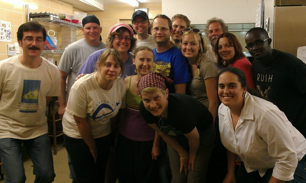 Volunteers posing in a commercial kitchen.