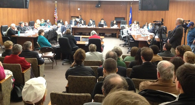 Photo of testimony in a crowded committee hearing room.