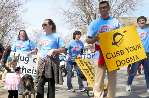 Photo of marchers in parade wearing MNA logo shirts. Sign (Curb your dogma) prominent in the foreground.