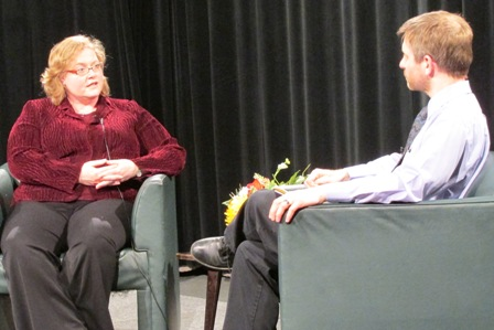 Photo of guest and host sitting in armchairs, talking.