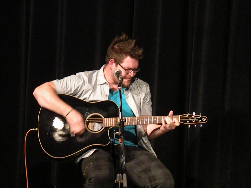 Photo of Tuthill playing guitar.
