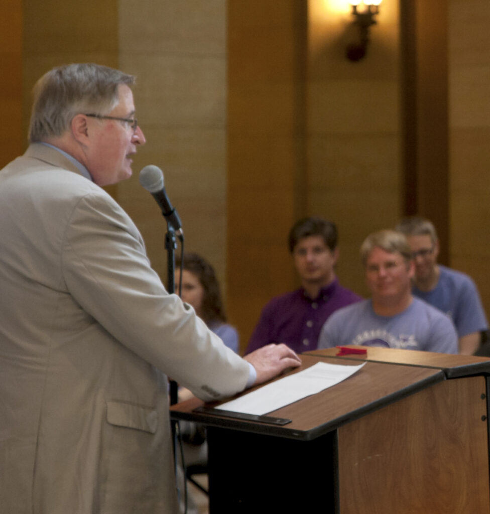 Photo of speaker at a podium showing audience in the background.
