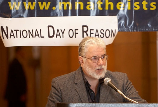 Photo of Jim Barri at podium in front of Day of Reason banner.