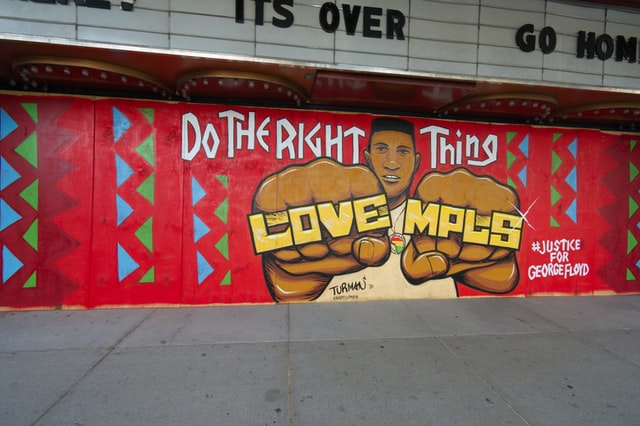 """Photo of mural on boarded up Uptown theater. Caption """"Do the right thing"""" above a Black man whose rings read """"Love Mpls."""""""