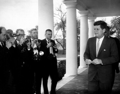 B&W photo of JFK talking to the press outside the White House.