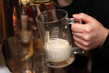 Photo of hand holding a glass stein at a tap. The glass is about a third full of foam.