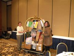 Photo of two women pushing a luggage cart full of donations.