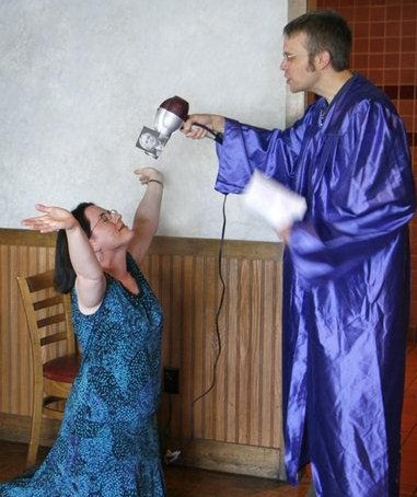 """Photo of MNA member being """"de-baptised"""", kneeling and with her hands in the air."""
