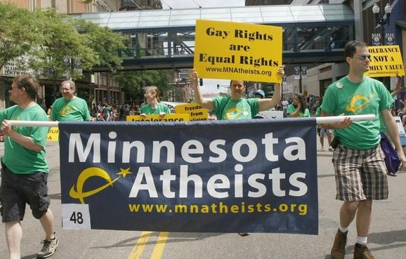 Photo of marchers in MNA shirts with the org banner in the Pride parade.