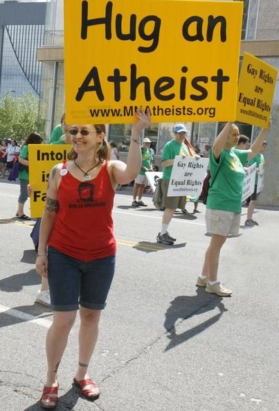"""Photo of MNA member marching with a """"Hug an Atheist"""" sign."""
