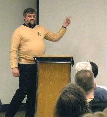 Photo of Scott speaking at the podium, wearing a Star Trek shirt.