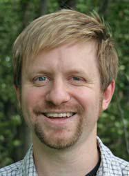 Headshot of James smiling.