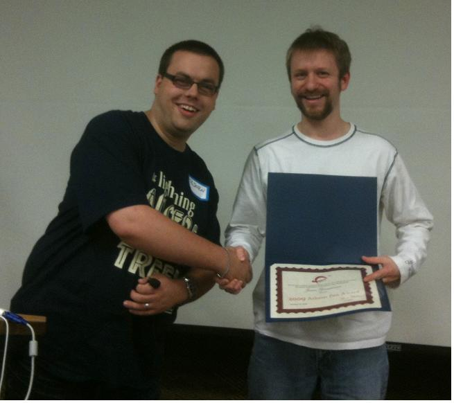 Photo of Bjorn presenting the certificate to James.