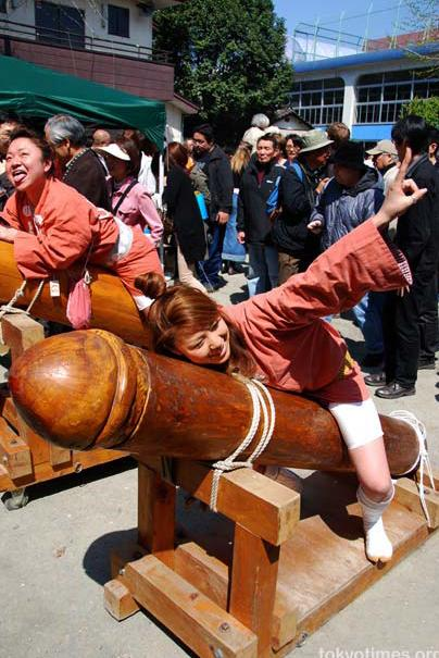 Photo from Japanese festival, featuring young women lying on wooden phalluses larger than they are.