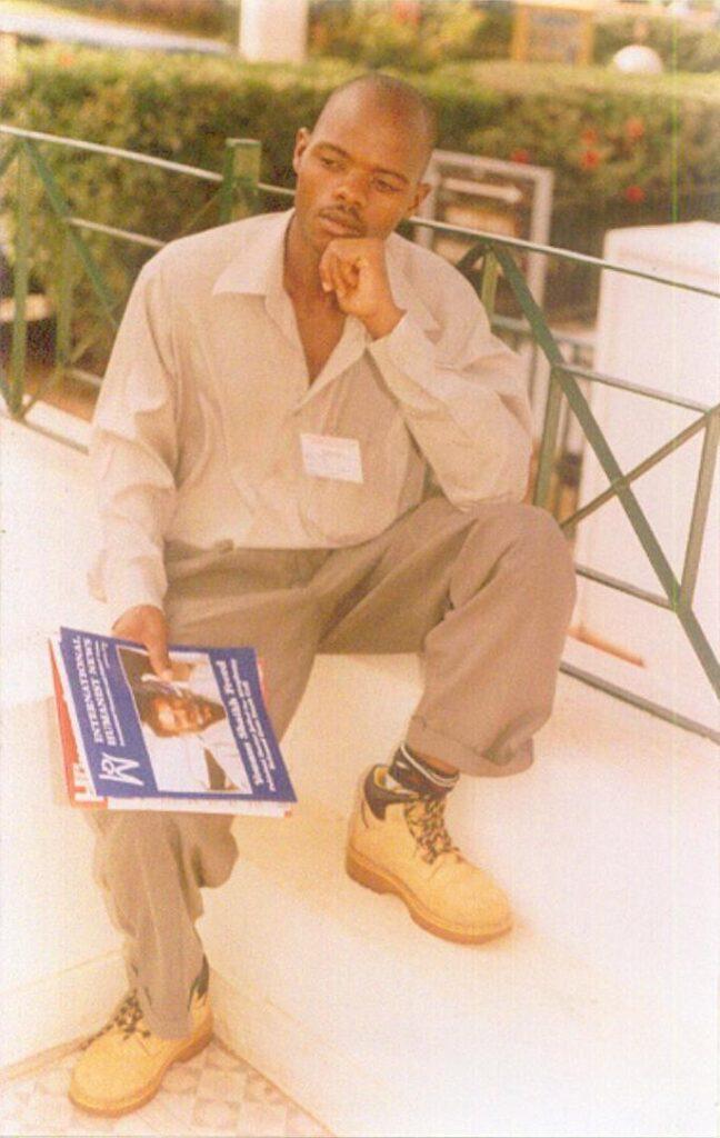 Photo of Kirumira sitting on stairs.