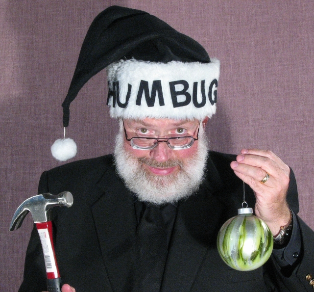 """Photo of Tom wearing a black """"Santa"""" hat that reads """"Humbug"""" and menacing a Christmas ornament with a hammer."""
